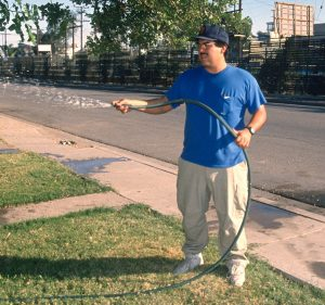Image of Photographer Jimmy Dorantes in his childhood home's front yard, watering grass in front of the border fence where he grew up with a camera often in hand.